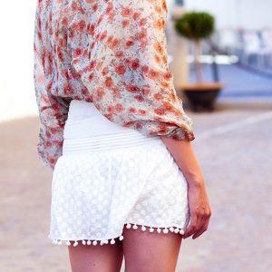 falda blanca corta con borlas redondas en la parte inferior