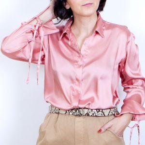 Camisa de raso rosa de manga larga con botonadura delantera invisible. Tiene lazada en los puños.